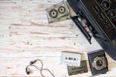 Игрок, кассетный магнитофон и лента звукозаписи кассеты на деревянном ба Стоковые Фото