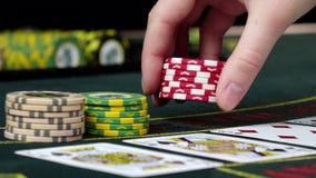 Игрок на казино держит пари его обломоки играя покер, конец вверх сток-видео