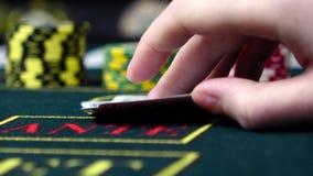 Игрок проверяет его покер играть карточек, конец вверх, вид спереди сток-видео
