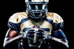 Игрок спортсмена американского футбола изолированный на черной предпосылке стоковые изображения rf
