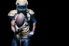 Игрок спортсмена американского футбола изолированный на черной предпосылке стоковое фото rf