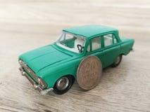 Игрушка автомобиля модельная по сравнению со старой монеткой стоковые фото