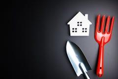 Игрушка Белого Дома и садовничая инструменты на черной предпосылке с полисменом Стоковые Фотографии RF