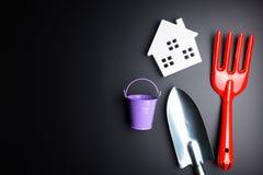 Игрушка Белого Дома и садовничая инструменты на черной предпосылке с полисменом Стоковое Изображение