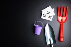 Игрушка Белого Дома и садовничая инструменты на черной предпосылке с полисменом Стоковая Фотография