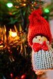 Игрушка гнома как украшение зимних отдыхов против несосредоточенного дерева ` s Нового Года с гореть праздничную гирлянду освещае стоковое фото