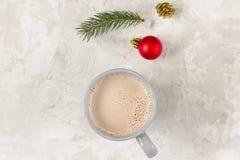 Игрушка ели, ветви ели и чашка какао на конкретной предпосылке Стоковая Фотография