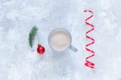 Игрушка ели, ветви ели и чашка какао на конкретной предпосылке Стоковое фото RF