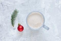 Игрушка ели, ветви ели и чашка какао на конкретной предпосылке Стоковое Фото