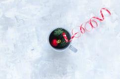 Игрушка ели, ветви ели и чашка на конкретной предпосылке Стоковые Фотографии RF