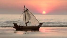 Игрушка маленькой лодки на пляже песка на заходе солнца видеоматериал
