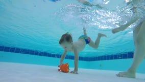 Игрушка получает поднятой от дна бассейна младенцем сток-видео