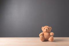 Игрушка плюшевого медвежонка самостоятельно на древесине в передней серой предпосылке Стоковая Фотография