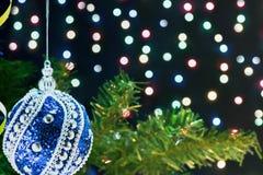 Игрушка рождества на ветви дерева на предпосылке освещает Стоковые Фото