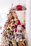 Игрушка Санта Клауса на парашюте приносит подарки на красную предпосылку bokeh рождественской елки Большое знамя Нового Года конц стоковые фотографии rf