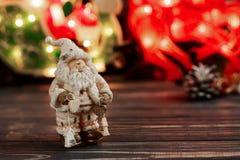 Игрушка Санта Клауса рождества на предпосылке гирлянды освещает на bla Стоковая Фотография