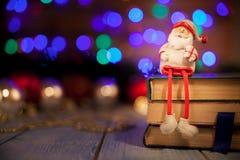 Игрушка Санта Klaus с подарком сидит на книгах стоковая фотография