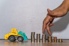 Игрушка трактора загружая стог монеток, руку как палец бежать на куче монеток Стоковое Изображение RF
