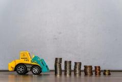 Игрушка трактора загружая стог монеток Стоковое фото RF