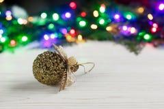 Игрушка шарика рождества золотая на предпосылке красочного ligh гирлянды Стоковые Фото