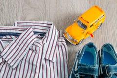 Игрушка школьного автобуса около рубашек и голубых ботинок шлюпки на серой деревянной предпосылке Обмундирование мальчика конец в Стоковое Изображение RF