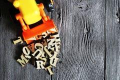 Игрушка экскаватора и деревянные письма на деревянном столе стоковые изображения