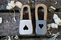 Игрушка Handmade padlock деревянная На деревянной предпосылке с деревянными shavings Красивый keyhole в форме сердец и Стоковая Фотография