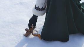 Игрушка ` s детей лежа в снеге и женщина принимают его Маленькая игрушка снеговика в снеге Рука принимает игрушку рождества ретро Стоковые Изображения RF