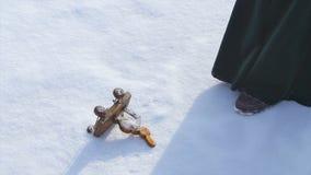 Игрушка ` s детей лежа в снеге и женщина принимают его Маленькая игрушка снеговика в снеге Рука принимает игрушку рождества ретро Стоковые Фото