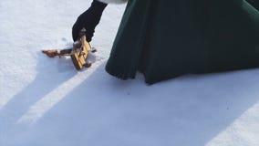 Игрушка ` s детей лежа в снеге и женщина принимают его Маленькая игрушка снеговика в снеге Рука принимает игрушку рождества ретро Стоковое Фото