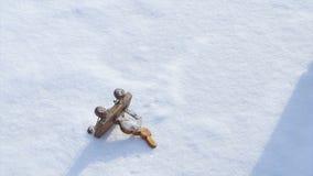 Игрушка ` s детей лежа в снеге и женщина принимают его Маленькая игрушка снеговика в снеге Рука принимает игрушку рождества ретро Стоковое Изображение RF