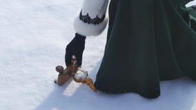 Игрушка ` s детей лежа в снеге и женщина принимают его Маленькая игрушка снеговика в снеге Рука принимает игрушку рождества ретро акции видеоматериалы