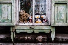 Игрушки детей на старом окне деревни стоковое фото rf