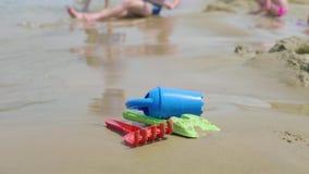 Игрушки детей на тропическом пляже песка, семейном отдыхе Пластиковая игрушка лопаткоулавливателя для игры ребенк на стороне моря сток-видео