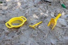Игрушки желтого цвета в ящике с песком Стоковые Изображения RF