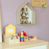 Игрушки на деревянном столе с картинной рамкой и полки на стене Стоковое фото RF