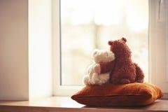 2 игрушки плюшевого медвежонка обнимать сидя на окн-силле Стоковое Изображение RF