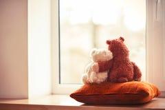 2 игрушки плюшевого медвежонка обнимать живущих сидя на окн-силле Стоковая Фотография RF