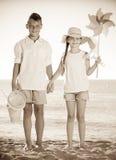 Игрушки пляжа мальчика и девушки стоящие Стоковое Фото