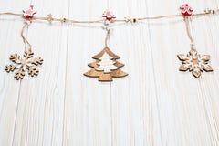 Игрушки рождества деревянные в форме рождественской елки и снежинок весят на веревочке на белой деревянной предпосылке Стоковые Изображения