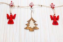 Игрушки рождества деревянные в форме рождественской елки и снежинок весят на веревочке на белой деревянной предпосылке Стоковые Фотографии RF