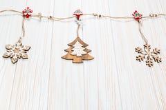 Игрушки рождества деревянные в форме rope на белой деревянной предпосылке Красивая праздничная поздравительная открытка Стоковое Изображение RF