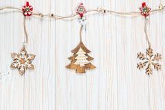 Игрушки рождества деревянные в форме rope на белой деревянной предпосылке Красивая праздничная поздравительная открытка Стоковые Изображения RF