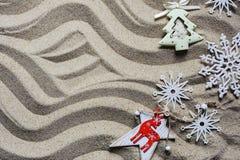Игрушки рождества лежат на песке пляжа, взгляде сверху стоковые изображения rf