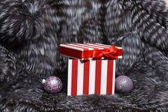 Игрушки рождества и присутствующая коробка на мехе Стоковое Изображение