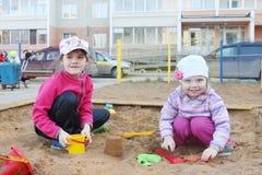 2 игры девушек в ящике с песком на спортивной площадке детей Стоковое фото RF
