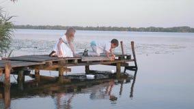 Игры детей, милые друзья мальчик и девушка на деревянном мосте позволяя на паруснике бумаги реки воды во время на открытом воздух видеоматериал