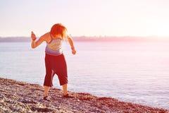 Игры девушки на пляже моря Стоковое Изображение