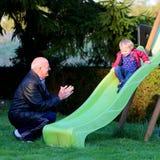 Игры деда с внучкой на спортивной площадке стоковые фото