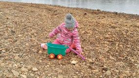 Игры маленькой девочки на камнях побережья видеоматериал